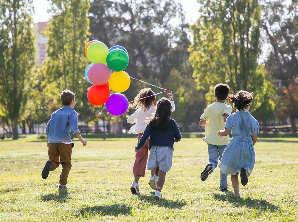 Children playing outside with balloons