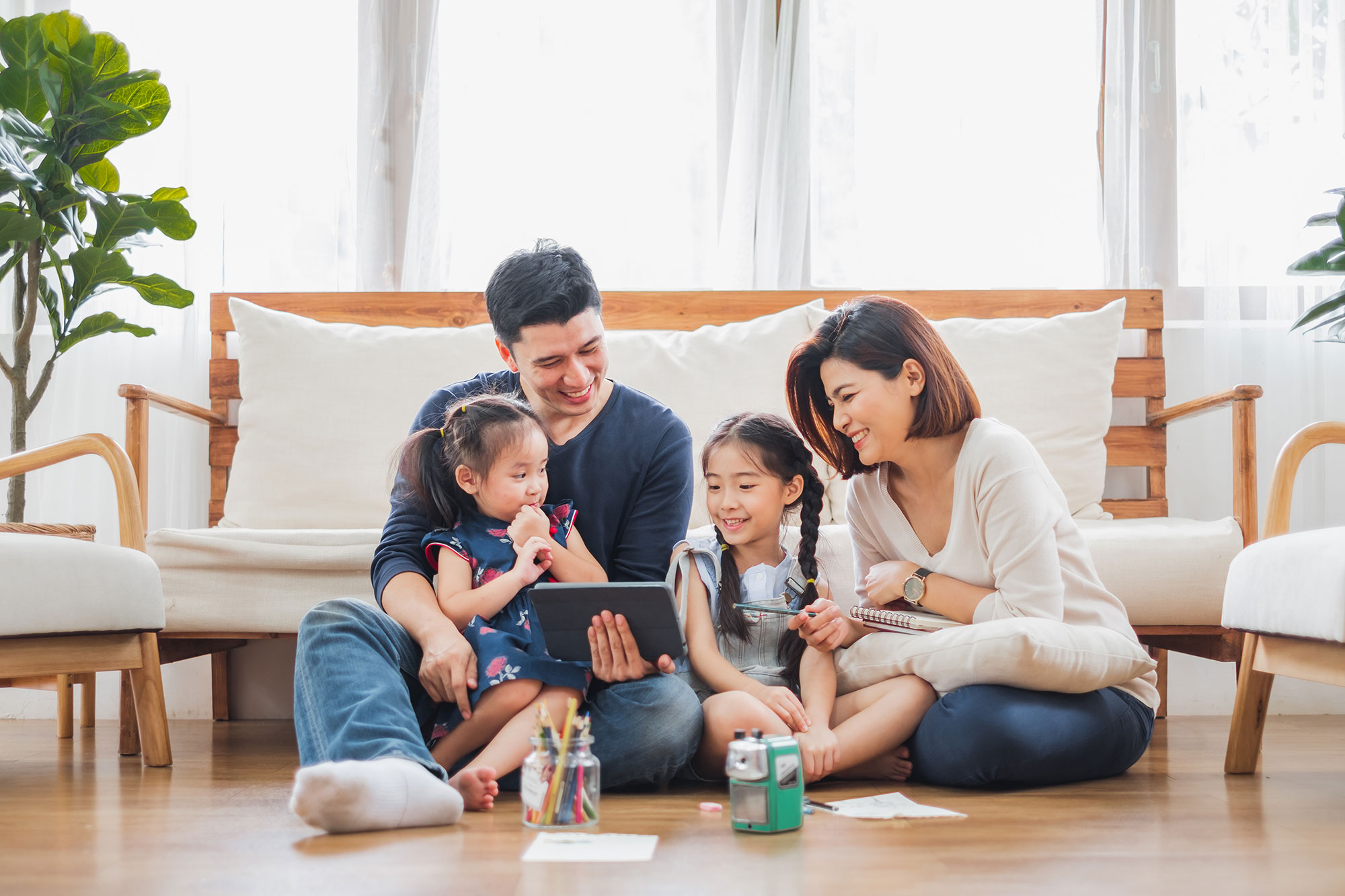 Family sitting on the floor looking at their tablet device together