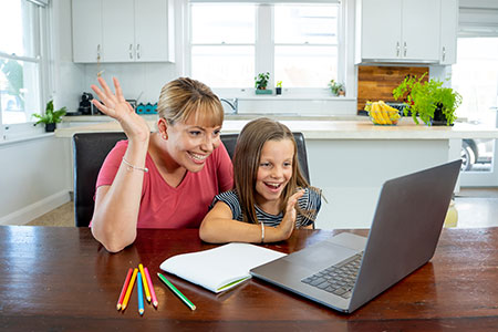 Mum and daughter using their laptop to attend an online event