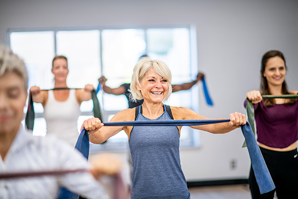Woman at a group fitness gym class with resistance band